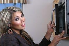 Frau, die Mikrowelle verwendet lizenzfreie stockbilder
