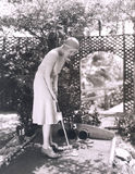 Frau, die Minigolf spielt Stockfotografie