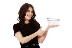 Frau, die Miniwarenkorb hält stockfoto