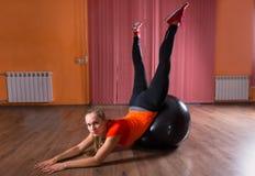Frau, die mit Übungs-Ball im Studio ausdehnt Lizenzfreie Stockfotos