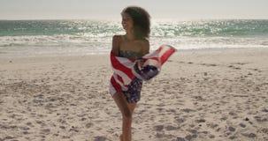 Frau, die mit amerikanischer Flagge auf dem Strand 4k läuft stock video
