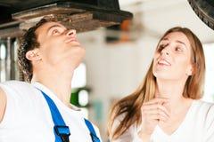 Frau, die mit Automechaniker in der Reparaturwerkstatt spricht Lizenzfreie Stockfotos