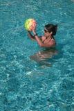Frau, die mit Ball in einem Swimmingpool spielt stockfoto