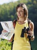 Frau, die mit Binokeln und Karte wandert Stockfotografie