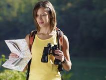 Frau, die mit Binokeln und Karte wandert lizenzfreie stockbilder