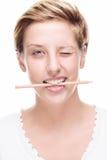 Frau, die mit Bleistift in ihrem Mund blinzelt Lizenzfreie Stockbilder