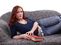 Frau, die mit Buch auf Couch sich entspannt Lizenzfreie Stockfotografie
