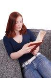 Frau, die mit Buch auf Couch sich entspannt Stockfotos