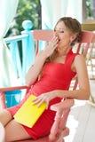 Frau, die mit Buch und dem Schwanken sitzt Lizenzfreie Stockfotos