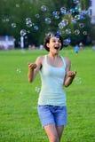 Frau, die mit bunten Seifenblasen spielt Lizenzfreies Stockfoto