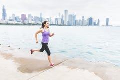 Frau, die mit Chicago-Skylinen auf dem Hintergrund, verschiebend rüttelt lizenzfreies stockfoto