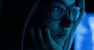 Frau, die mit Computer, dem Zerhacken und dem Schreiben arbeitet Bildschirm und Code reflektierten sich in Frau ` s Gläsern stock video footage
