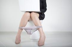 Frau, die mit Computer im Badezimmer arbeitet Stockfoto