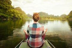 Frau, die mit dem Boot auf Fluss unter dem szenischen Karst mountai reist lizenzfreie stockfotografie