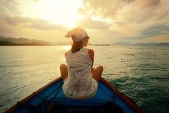 Frau, die mit dem Boot bei Sonnenuntergang unter den Inseln reist. Stockbild