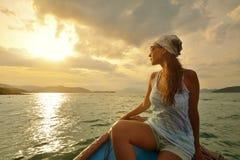Frau, die mit dem Boot bei Sonnenuntergang unter den Inseln reist. Lizenzfreie Stockfotos