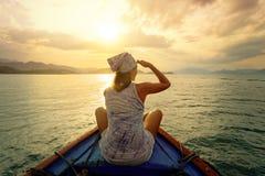 Frau, die mit dem Boot bei Sonnenuntergang unter den Inseln reist Lizenzfreies Stockfoto