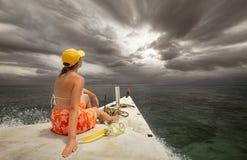 Frau, die mit dem Boot unter den Inseln vor Regen reist lizenzfreies stockbild