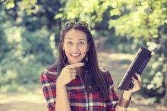 Frau, die mit dem Finger auf ihren Auflagencomputer zeigt Stockfotografie