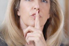 Frau, die mit dem Finger zu den Lippen zum Schweigen bringt Stockfotos
