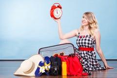 Frau, die mit dem Koffer hält alte Uhr sitzt Lizenzfreie Stockbilder