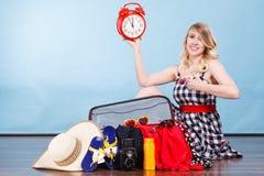 Frau, die mit dem Koffer hält alte Uhr sitzt Stockbild