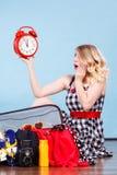 Frau, die mit dem Koffer hält alte Uhr sitzt Lizenzfreies Stockfoto