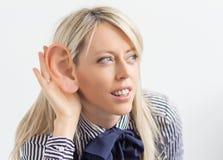 Frau, die mit dem lächerlich großen Ohr hört lizenzfreie stockfotos