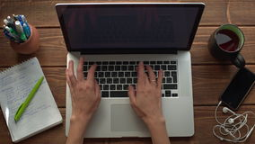 Frau, die mit dem Laptop gesetzt auf hölzernen Schreibtisch arbeitet stock video