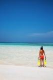 Frau, die mit dem Schnorcheln des Gangs auf dem Strand steht Stockbilder