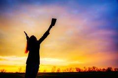 Frau, die mit den angehobenen Händen bleibt Lizenzfreies Stockfoto