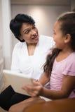 Frau, die mit der Enkelin verwendet digitale Tablette sitzt stockfoto