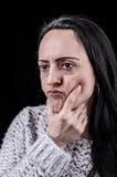 Frau, die mit der Hand auf Kinn denkt Lizenzfreie Stockfotografie