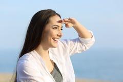 Frau, die mit der Hand auf Stirn auf dem Strand kundschaftet Stockbilder