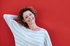 Frau, die mit der Hand hinter Kopf durch rote Wand steht lizenzfreies stockbild