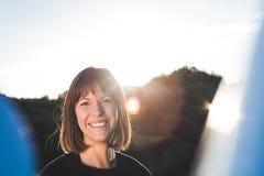 Frau, die mit der Sonne hinter ihr lächelt stockfotografie