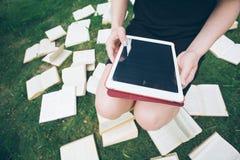Frau, die mit ebook Leser und Buch lernt Wahl zwischen moderner pädagogischer Technologie und traditioneller Weisenmethode Mädche stockbild