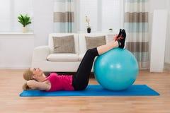 Frau, die mit Eignungs-Ball im Wohnzimmer trainiert Stockbild