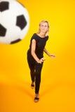 Frau, die mit einem Fußball spielt Stockfotografie
