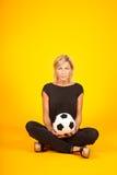 Frau, die mit einem Fußball spielt Stockbild