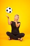 Frau, die mit einem Fußball spielt Lizenzfreie Stockfotos
