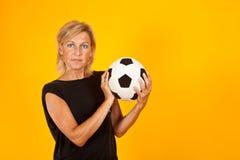Frau, die mit einem Fußball spielt Lizenzfreie Stockbilder