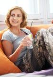 Frau, die mit einem Getränk am Restaurant sich entspannt Lizenzfreies Stockfoto