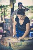 Frau, die mit einem großen Messer einige Kokosnusssüßigkeiten bearbeitet stockbild