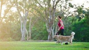 Frau, die mit einem Hund im Park läuft stock video