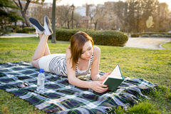 Frau, die mit einem Hut über ihrem Gesicht in einem Park schläft Stockfotografie