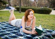 Frau, die mit einem Hut über ihrem Gesicht in einem Park schläft Stockbild
