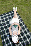 Frau, die mit einem Hut über ihrem Gesicht in einem Park schläft Stockbilder