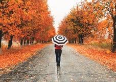 Frau, die mit einem Regenschirm auf der Straße im Herbst steht lizenzfreie stockbilder