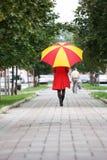 Frau, die mit einem Regenschirm geht lizenzfreie stockfotos